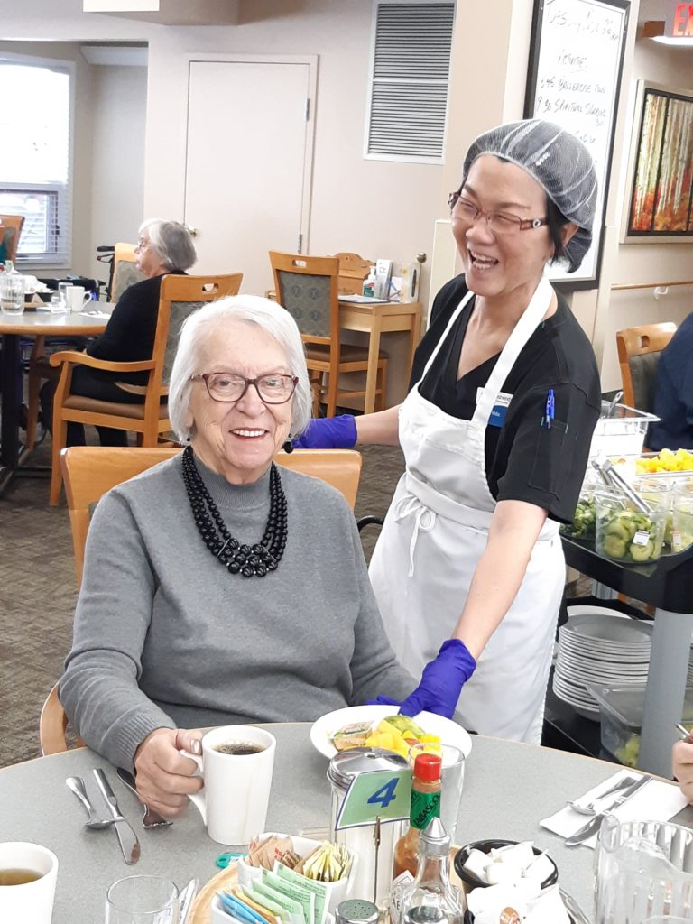 Westwinds Communities is a great place to work.  Image of staff member and resident at meal time.